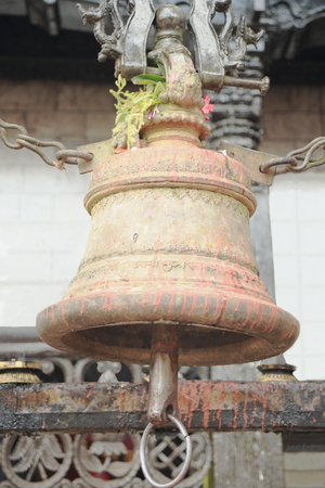 encircling: The bell -secured with iron chains- hangs from the second fence encircling the shrine and is often pealed by the faithfuls  In the Manakamana Mandir-Goddess Bhagwati-Heartwishes Temple  Nepal  Stock Photo
