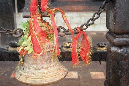 bell bronze bell: Gran campana de bronce y cintas rojas atadas ante una hilera de quemadores de incienso de cobre en la Manakamana Mandir. Diosa Bhagwati-Heartwishes templo-Nepal. Foto de archivo