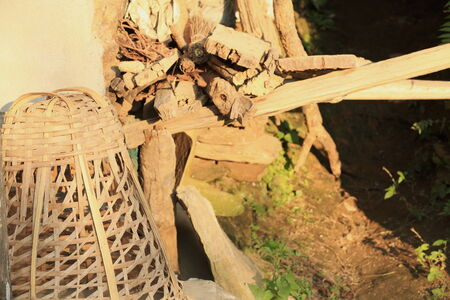traditionally: Traditionally woven wicker basket on the floor beside a small heap of firewood placed outside an old house in the outskirts of Bandipur Town-Tanahu District-Gandaki Zone-Nepal.