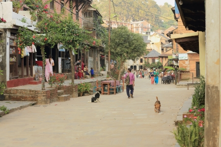 BANDIPUR, NEPAL - OCTOBER 6: Tourists and locals walk and sit along the cobblestone pedestrian central street at sundown while the cafes alongside begin to open on October 6, 2012 in Bandipur-Tanahu District-Gandaki Zone-Nepal.