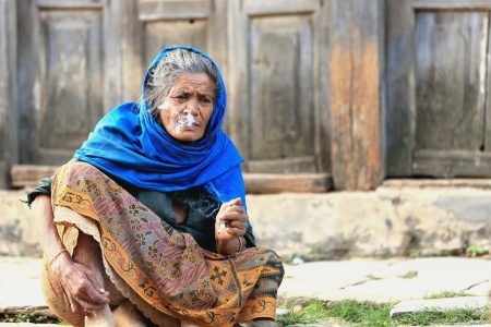 beauty contest: BANDIPUR, NEPAL - OCTOBER 6: Nepali old woman smokes a cigarette while looking at the contestants in the Banlamha Mayaju Newari Beauty Contest as they visit the town on October 6, 2012 in Bandipur-Tanahu District-Gandaki Zone-Nepal. Editorial