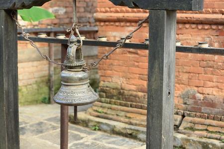 bell bronze bell: Campana de bronce que cuelga atado con cadenas de hierro colocados ante una hilera de incensarios de bronce en la calle central de la ciudad-Bandipur Tanahu Distrito-Gandaki Zone-Nepal Foto de archivo