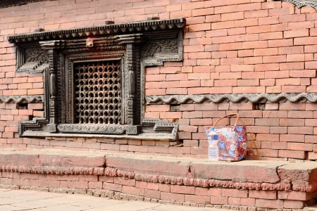 lattice window: Dark carved wood lattice window and snake frieze on the red brick facade of the Kalika Mandir in the Gorkha Durbar. Gorkha Town and District-Gandaki Zone-Nepal.