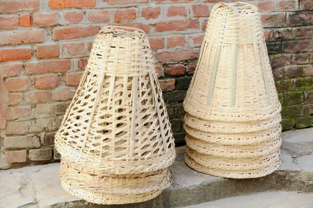 Hand made traditional wicker baskets on the sidewalk and leaning on the red brick wall of a traditional newari style house  Bandipur-Tanahu district-Gandaki zone-Nepal  photo