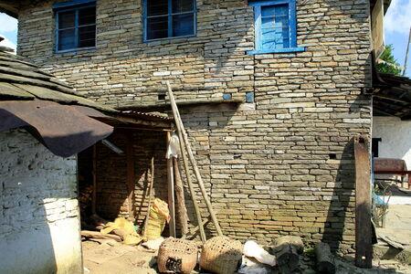 log basket: Stone walled house-homestead in downtown Dhampus village on the trek route around the Annapurnas range of the Himalayas  Kaski district-Gandaki zone-Nepal