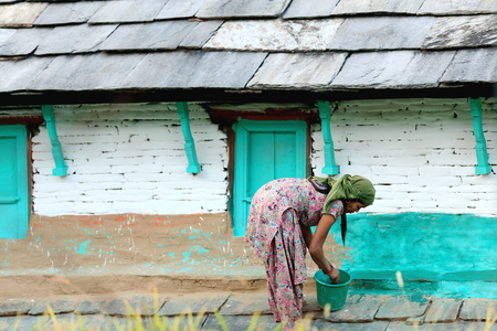 DHAMPUS, NEPAL - OCTOBER 8  Nepali woman paints her houses s facade in green on October 8, 2012 in Dhampus village on the Annapurnas Tour trekking route through the foothills of the Himalayas  Kaski district-Gandaki zone-Nepal