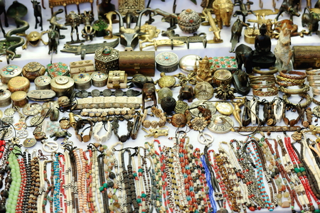 sidewalk sale: Nepali handicrafts-necklaces-bracelets-small boxes-animal figurines-buddhist images for sale in the windowshop of a store facing the sidewalk of a street in Pokhara city-Kaski district-Gandaki zone-Nepal.