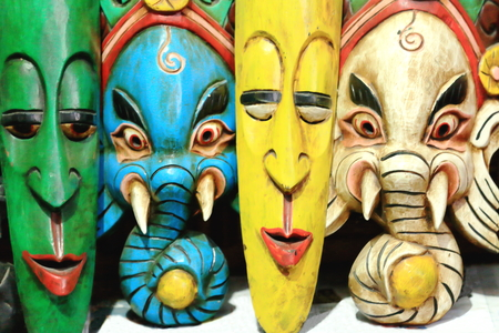 long faced: Colorfully painted carved wooden traditional masks representing god Ganesh in blue and white colors and along with two others of a long human face in green and yellow. Stock Photo
