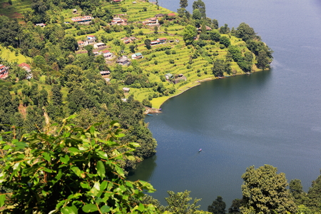 homesteads: View of some homesteads among orchards on the shore of the 4.43 km2-784 ms.high Phewa tal-lake seen from the way down Ananda Hill and opposite Pokhara city. Kaski district-Gandaki zone-Nepal.