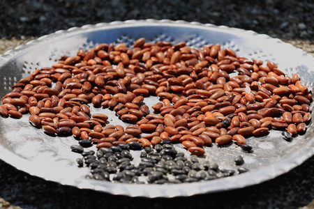 sapid: Bunch of red and black beans set to dry under he sun on a silvery tray. Homestead beside the 4.43 km2-784 ms.high Phewa tal-lake