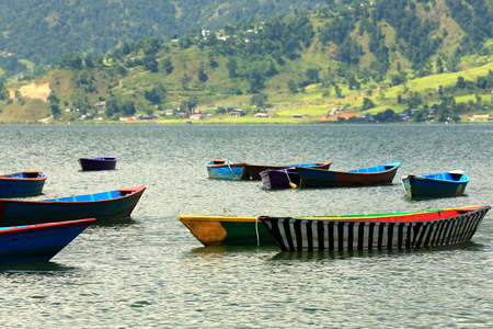 shallop: Colorist wooden rowboats wait for the tourists and the locals going for a pleasure ride on the banks of the 4.43 km2-784 ms.high Phewa tal-lake. Pokhara-Kaski distr.-Gandaki zone-Nepal