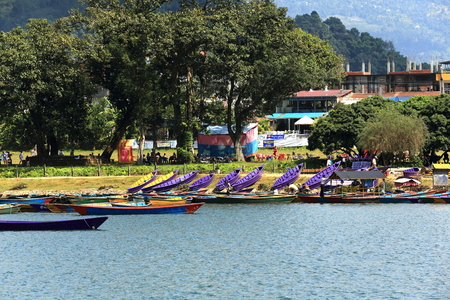 shallop: POKHARA, NEPAL - OCTOBER 12: Colorist wooden rowboats wait for the tourists and the locals going for a pleasure ride on the banks of the 4.43 km2-784 ms.high Phewa tal-lake on october 12, 2012 in Pokhara-Kaski distr.-Gandaki zone-Nepal.