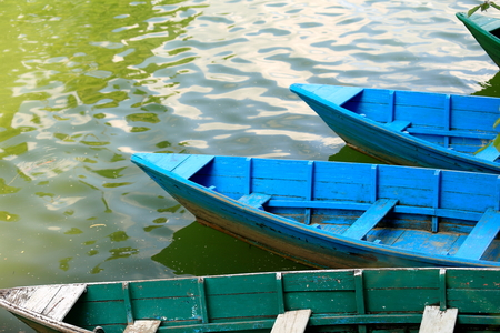 phewa: Blue and green colored wooden rowboats at the foot of Ananda hill on the shore of the 4.43 km2-784 ms.high Phewa tal-lake. Pokhara-Kaski district-Gandaki zone-Nepal. Stock Photo