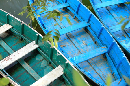 shallop: Blue and green colored wooden rowboats at the foot of Ananda hill on the shore of the 4.43 km2-784 ms.high Phewa tal-lake. Pokhara-Kaski district-Gandaki zone-Nepal Stock Photo