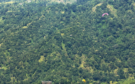 phewa: Yellow and purple paragliders fly the skies over the 5.23 km2 Phewa tal-lake jumping from the lesser slopes of the Annapurnas range on the foothills of the Himalayas. Pokhara-Kaski district-Gandaki zone-Nepal. Stock Photo