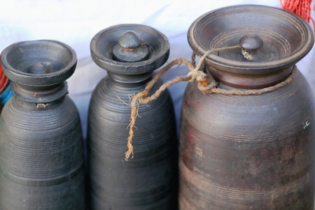 cylindrical: Cylindrical hand crafted pottery big vessels containing some liquids-rope tied lids for sale in a liquid goods store of Pokhara-Kaski district-Gandaki zone-Nepal. Stock Photo