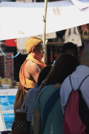 POKHARA, NEPAL - OCTOBER 12: Hindu sadhu of mongoloid ethnicity among tourists buys some handicrafts in a street stall by Patale Chhango on October 12, 2012 in Pokhara-Kaski distr.-Gandaki zone-Nepal.
