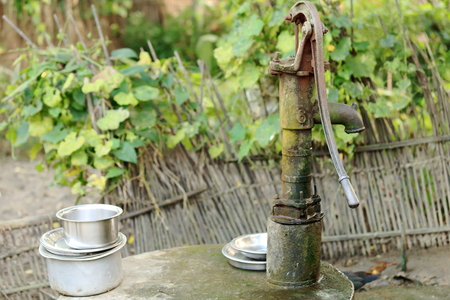 pileup: Old cast iron hand water pump along with some aluminum pans to wash them up on the rear grove surrounded by a reed fence of a traditional Tharu style house in Patihani-Chitwan distr.-Narayani zone-Nepal.