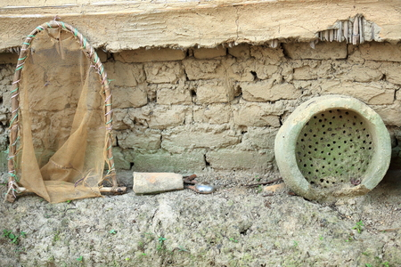 townhome: Old household items-clay colander and net on wooden frame leaning on the outer-stone based-mud covered-reed substructure rear wall of traditional townhome of the mongoloid Tharu people of the Terai area. Patihani-Chitwan distr.-Narayani zone-Nepal.