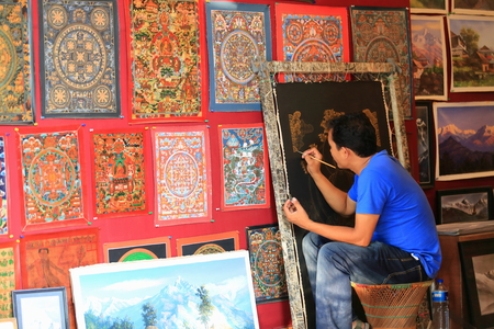 POKHARA, NEPAL - OCTOBER 12: Local artist paints a thangka over a black canvas tied with thin rope strings to a wooden frame in a souvenir shop selling also landscape images. Pokhara-Kaski distr.-Gandaki zone-Nepal.
