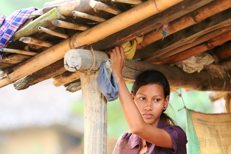 substructure: PATIHANI, NEPAL - OCTOBER 13: Young woman of the tharu people hangs her laundry from the bamboo and reef substructure of the roof of a shed on October 13, 2012 in Patihani-Chitwan distr.-Narayani zone-Nepal.