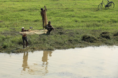 turbid: CHITWAN, NEPAL - OCTOBER 14: Local fishermen throw a cast net for fishing into a pond beside the Terai river on Octobeer 14, 2012 in the Bufferzone of the Chitwan Nnal.Park. Narayani zone-Nepal.