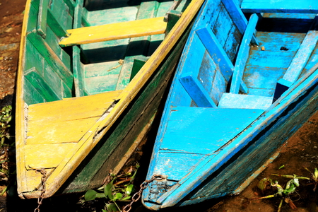 Yellow-green and blue colored wooden rowboats chained to a stake at the foot of Ananda hill on the shore of the 4.43 km2-784 ms.high Phewa tal-lake. Pokhara-Kaski district-Gandaki zone-Nepal