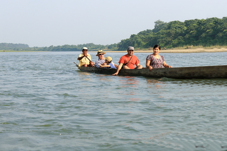 shallop: CHITWAN, NEPAL - OCTOBER 14: Tourists on wooden rowboats visit the Terai area by going down the Rapti river flowing through the bufferzone off the Chitwan Nnal.Park on October 14, 2012. Chitwan district-Narayani zone-Nepal. Editorial