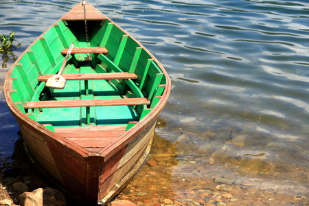 Red-green colored wooden rowboat chained to a stake on the shore of the 4.43 km2-784 ms.high Phewa tal-lake at the foot of Ananda Hill. Pokhara-Kaski district-Gandaki zone-Nepal. Stock Photo