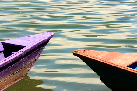rowboats: Red-blue and purple colored wooden rowboats stranded on the shore