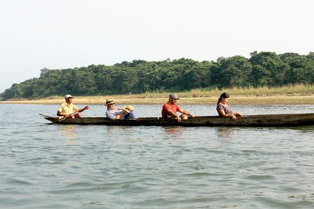 rowboats: CHITWAN, NEPAL - OCTOBER 14: Tourists on wooden rowboats visit the Terai area by going down the Rapti river flowing through the bufferzone off the Chitwan Nnal.Park on October 14, 2012. Chitwan district-Narayani zone-Nepal. Editorial