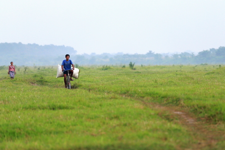 cycler: CHITWAN, NEPAL - OCTOBER 14, 2014: Nepalese man transports a hay pack on the grid of a bicycle with his wife walking behind through a trail in the field on the right bank of the Rapti river in the Terai area off the Chitwan Nnal.Park on October 14, 2012 i