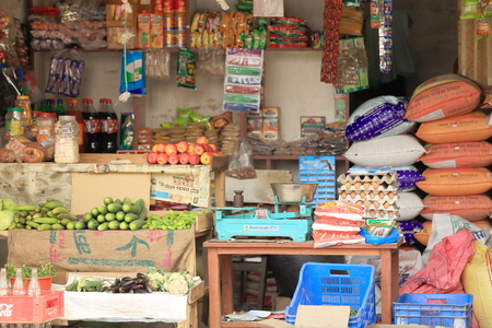 GODAWARI, NEPAL - OCTOBER 15: Grocery shop open to the street shows foodstuff items for sale: eggs-apples-cucumbers-eggplants-cauliflowers-zucchini-courgettes-candies-refreshment bottles and cans-juice bricks-bagels along with rice bags and and old blue p