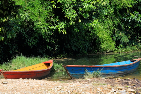rowboats: Red-yellow and blue-red colored wooden rowboats stranded on the shore of the 4.43 km2-784 ms.high Phewa tal-lake at the foot of Ananda Hill. Pokhara-Kaski district-Gandaki zone-Nepal.