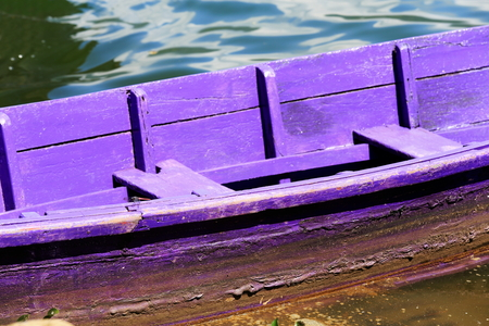 Purple colored wooden rowboat stranded on the shore of the 4.43 km2-784 ms.high Phewa tal-lake at the foot of Ananda Hill. Pokhara-Kaski district-Gandaki zone-Nepal. Stock Photo