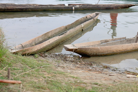 fettered: Wooden rowboats in the Safari Narayani Lodge stranded on the banks of the Rapti river used for the tourist traffic visiting the bufferzone off the Chitwan Nnal.Park in the Terai area. Ghatgain-Patihani-Chitwan distr.-Narayani zone-Nepal. Stock Photo