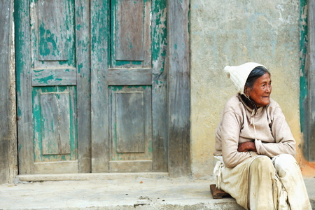 GODAWARI, NEPAL - OCTOBER 15: Old nepalese woman sits on the floor before the paint faded green door of her house in a street of Godawari on October 15, 2012. Lalitpur distr.-Bagmati zone-Nepal. Editorial