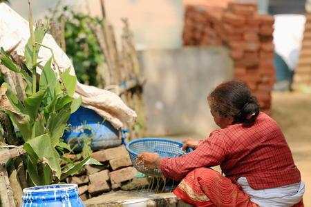 agachado: NAMO BUDA, NEPAL - 16 de octubre: La mujer mayor lava soja con un tamiz en el patio trasero de la parte superior de la AD-1978 VVKhenchen Thrangu Rinpoche fund� Thrangu Tashi Yangtse monasterio budista, el 16 de octubre de 2012. Namo Buda Kavrepalanchok d