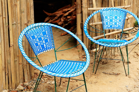 woodshed: White-blue chairs made of plastic braided over metal frame nestled at the door of a woodshed. Hamlet grown in the rear part of the 1978 AD-V.V.Khenchen Thrangu Rinpoche founded Thrangu Tashi Yangtse monastery. Namo Buddha-Kavrepalanchok distr.-Bagmati zon