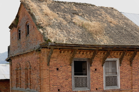obsolescence: Traditional newar style-red brick-roof tiles sprinkled with grass-old house with blind arches and windows in the old city area.