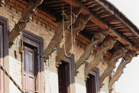 struts: Carved wooden roof struts in the traditional newar style on the red brick facade of house in the old city area. Dhulikhel-Kavrepalanchok distr.-Bagmati zone-Nepal.