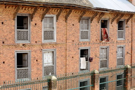 Traditional style carpets hanging on red brick walls of traditional Newar style buildings-paint faded windows and roof struts. Dhulikhel-Kavrepalanchok distr.-Bagmati zone-Nepal.