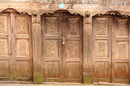 Paint faded-profusely carved wooden doors showing podery mildew fungus at the base. Closed shop in the old city area. Dhulikhel-Kavrepalanchok district-Bagmati zone-Nepal.