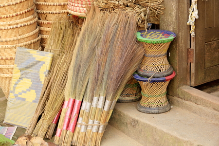 Traditional hand made wicker broom-woven wicker stools-baskets for sale at the door of a shop selling handicrafts in the old city area. Dhulikhel-Kavrepalanchok distr.-Bagmati zone-Nepal.