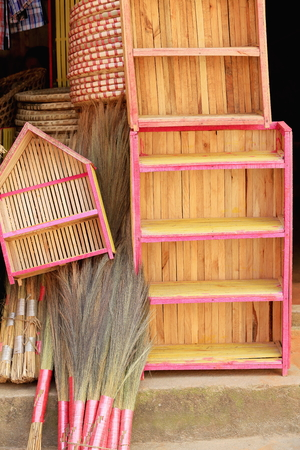 Traditional hand-made wooden cupboards wicker trays-brooms on the entrance steps to a nepalese handicraft selling shop in the old city area. Dhulilhel-Kavrepalanchok distr.-Bagmati zone-Nepal.