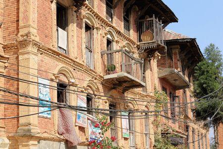 plundering: DHULIHEL, NEPAL - 16 oktober: Traditionele Newar stijl huizen tonen enkele advertenties op hun rode bakstenen gevels tegenover de oude stad gebied op 16 oktober 2012 in Dhulikhel-Kavrepalanchok distr.-Bagmati-Nepal.