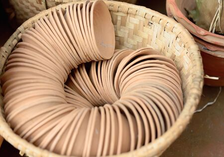 shop for animals: Set of small terracotta bowls placed in a spiral row in a wicker basket on the outside of a local handicrafts shop in the old city area. Panauti-Kavrepalanchok dstr.-Bagmati zone-Nepal Stock Photo