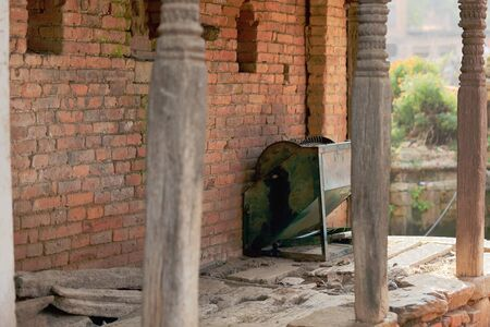 disuse: Unidentified old metallic agricultural device set aside under the arcade of an old red brick building in the old city area. Panauti-Kavrepalanchok dstr.-Bagmati zone-Nepal.
