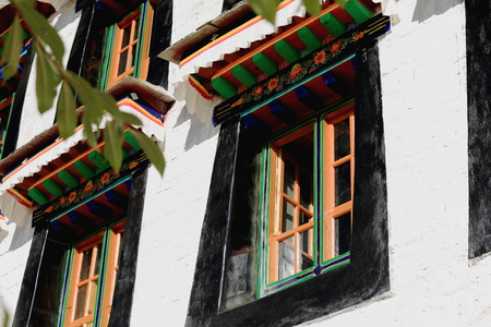 gelugpa: Colorist wooden windows on the white washed walls of the Drepung-Rice heap buddhist monastery of the Gelugpa-Yellow Hat School at the foot of mount Ghephel. Lhasa pref.-Tibet A.R.-China.