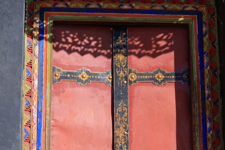 gelugpa: Red painted wooden door with black and gold painted decoration batten and colorist door frame in the Drepung-Rice Heap monastery of Gelugpa-Yellow Hat School at the foot of mt.Ghephel. Lhasa pref.-Tibet A.R.-China. Stock Photo